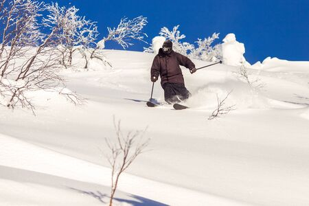 Skier skiing downhill during sunny day in mountains and forest. Extreme winter sports Banque d'images - 132272045