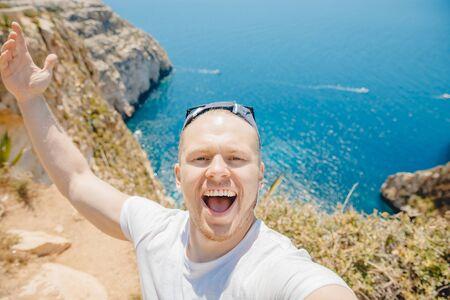 Happy tourist man smiles taking selfie photo on background Blue Grotto in Malta. Mediterranean travel concept