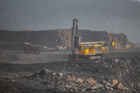 Open mine coal and minerals from bowels soil explosion. Drilling rigs borer drill wells for installing cast explosives blasting.