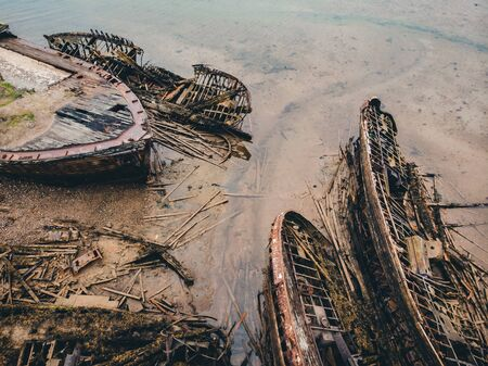 Cemetery of old ships Teriberka Murmansk Russia, wooden remains of industrial fishing boats in sea. Industrialization concept. Aerial top view. Imagens