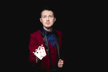 Magician shows focus, holds two playing cards in hand, copy space black background