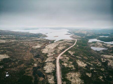 Dramatic scene, road Murmansk region through tundra, direction to Teriberka. Aerial top view