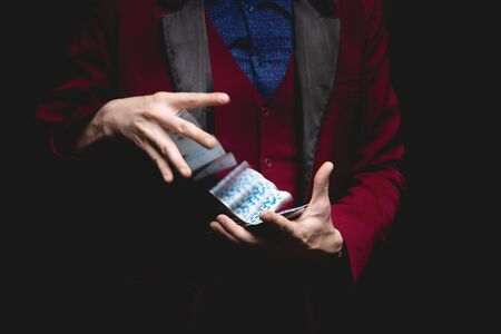 Magician shows trick with playing cards on dark background, copy space