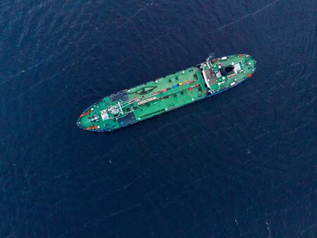 Oil chemical tanker sails blue sea fog. Aerial top view