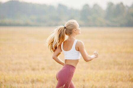 Haare flattern im Wind blondes Mädchen Läufer Morgendämmerung, Konzepttraining Standard-Bild