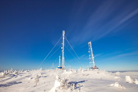 Weather meteorological station North, antennas in snow, blue clear sky