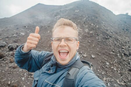 Tourist takes selfie on top of volcano Mount Etna, Sicily Italy. Mountain travel concept