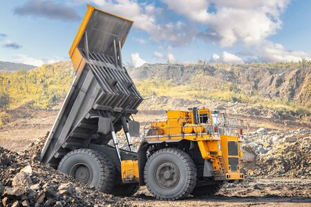 Open pit gold mine, big yellow mining truck moves ore.