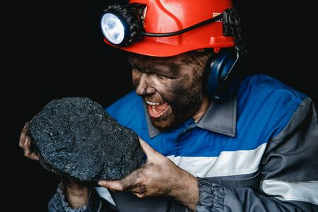 Miner man worker holds coal palm. Concept mining