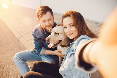 Happy beautiful couple is having fun with labrador dog retriever outdoors making selfie photo Imagens