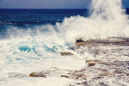 Waves and foam on surface of blue turquoise ocean water after storm, natural background.