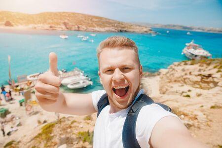 Male tourist sunglasses taking selfie photo on beach Blue Lagoon Comino Malta water mediterranean sea