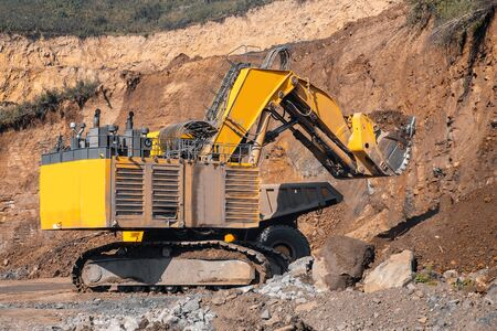 Loader excavator during earthmoving works loads soil ground into large yellow dump truck. Concept open mine.