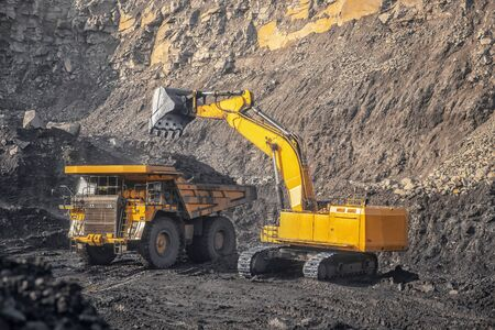 Open pit mine industry, excavator loading coal on big yellow mining truck for anthracite. Banco de Imagens - 132123407