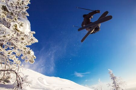 Skier jumps in fresh snow freeride in mountains against background forest. Extreme sport concept Banque d'images - 132273539