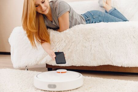 Young girl using automatic robot vacuum cleaner working on carpet. Controlling smart home functions with phone Stok Fotoğraf