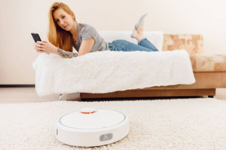 Young girl using automatic smart robot vacuum cleaner working on carpet Stok Fotoğraf
