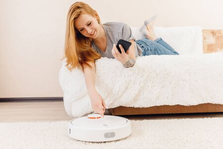 Young girl using automatic smart robot vacuum cleaner working on carpet. Controlling device with phone Stok Fotoğraf