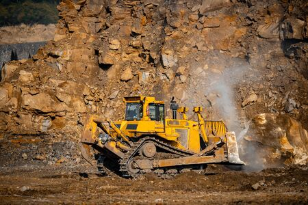 Grader excavator removes large stones after rock explosion blasting