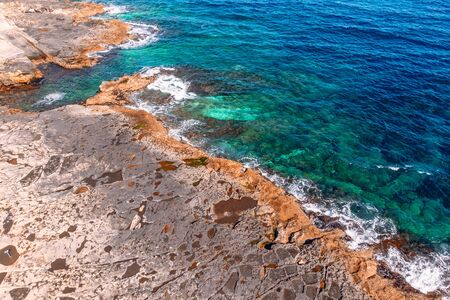 Top view Azure blue sea with waves beating on beach and rocks. Aerial photo Banco de Imagens
