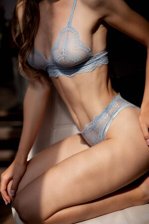 Beautiful young woman in dark blue lace underwear sitting on chair posing