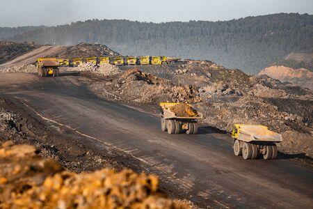 Duża żółta ciężarówka górnicza na antracyt. Kopalnia odkrywkowa, przemysł wydobywczy węgla Zdjęcie Seryjne