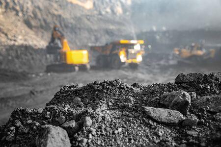 Miniera di carbone a cielo aperto. Sullo sfondo sfocato caricamento escavatore di minerali antracite in un grande camion giallo. Archivio Fotografico