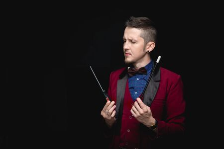 Male magician is experimenting with magic wands using screwdriver tool, black background
