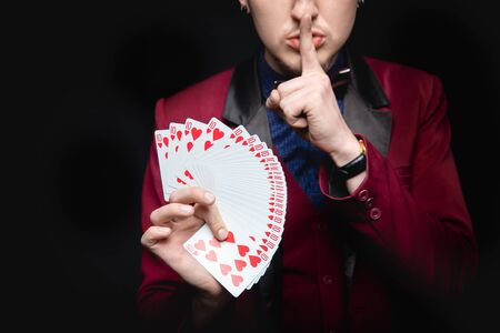 Disclosure of focus. Magician shows trick with playing same cards on dark background.