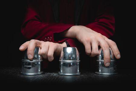 El mago muestra el juego de conchas de dedales con círculos y bolas, fondo negro. Concepto de engaño, prestidigitación. Foto de archivo