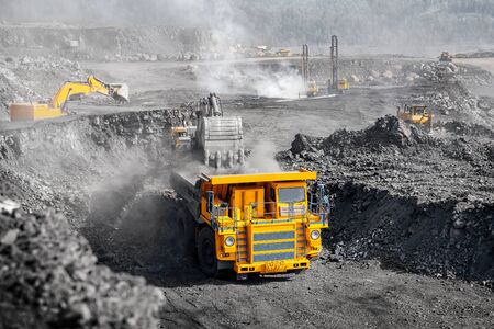 Open pit mine industry, big yellow mining truck for coal anthracite. Banco de Imagens