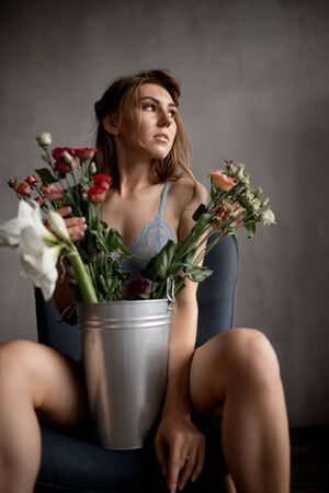Beautiful young woman in lace blue underwear holds rose flowers, skin care concept Stockfoto