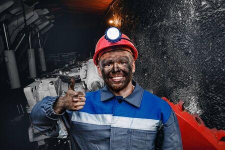 Retrato de trabajo joven minero en gorra roja mostrando los pulgares para arriba, excelente signo fondo mina de carbón. Concepto industrial