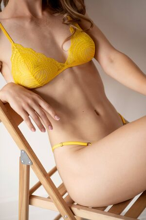 Yellow underwear. Beautiful young woman with clean skin sits on chair, concept handmade work making bra and panties