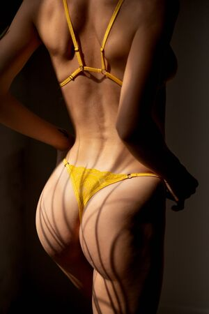 Beautiful young woman in yellow underwear with lace straightens panties
