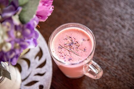 Pink lavender latte coffee in glass mug with flowers, top view.