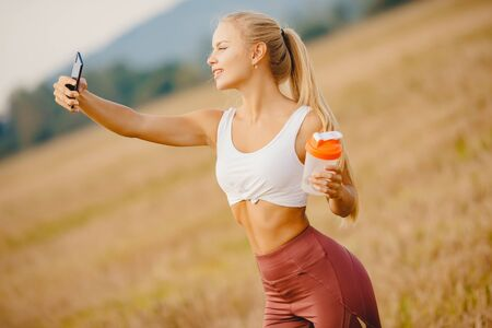 Beautiful blonde girl makes selfie photo on phone during sports training, smiling camera Stock Photo
