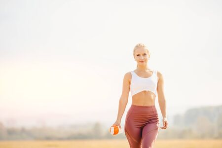 Beautiful athletic girl runner holds water bottle and looks into frame, background park Stock Photo