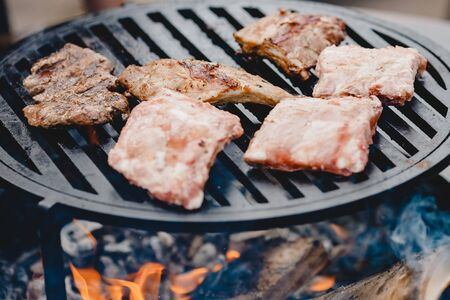 Pork ribs and steak cooked on grill, open fire street food festival.