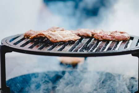 Cook grills steaks and pork ribs open fire. Turns meat over with tongs. Street food concept.