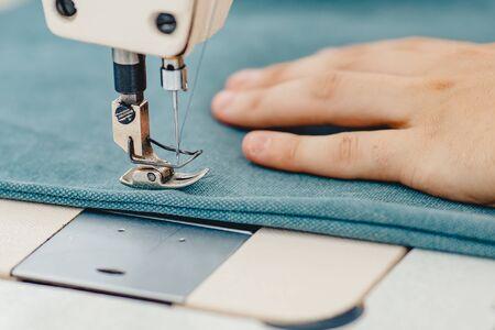 Männliche Hände schneidern an Nähmaschine und machen Einkaufstasche aus Stoff.