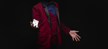 Magician young man holds playing cards in red jacket on black background