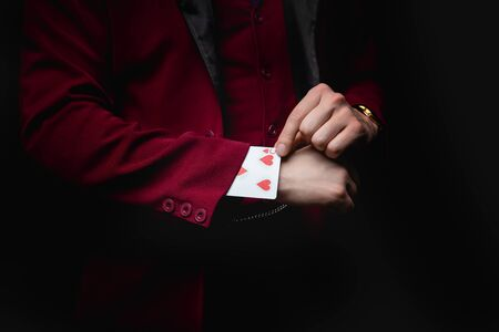 Magician shows trick with playing cards, disappearance in sleeve 写真素材