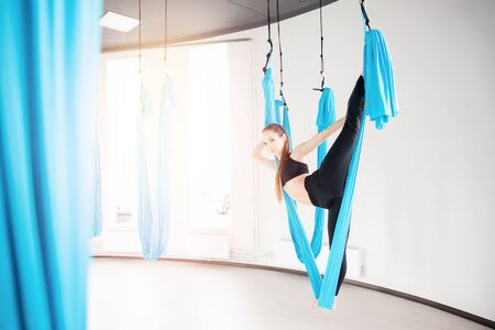 Young woman performing antigravity aerial yoga exercise in white studio. Concept meditation Stok Fotoğraf