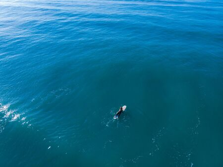Athlete in wetsuit on surfboard floats one middle of huge turquoise sea. Lifestyle. Top view aerial drone