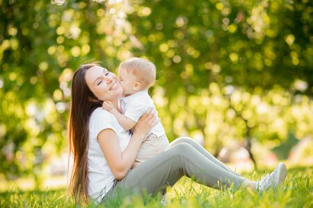 Happy family, little boy kisses his mother for walk in summer park. Childhood concept