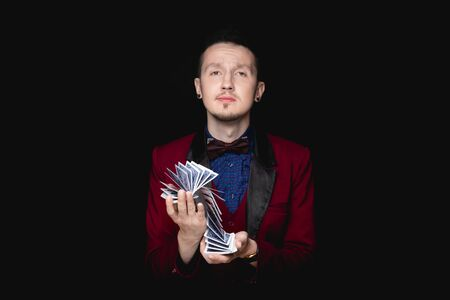 Magician shows focus with playing cards on black background
