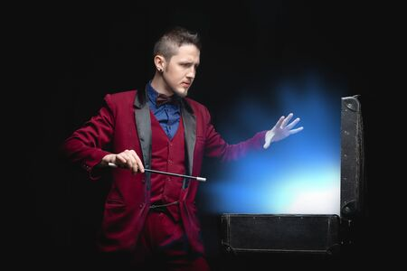 Magician man with magic wand shows disappearance in suitcase blue glow light on black background