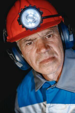 Portrait happy man miner after working in coal mine, dirty face in helmet. Concept vocation industrial worker 写真素材