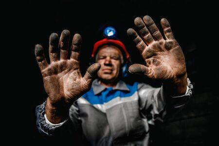 Miner dirty hands after working on coal mine. Concept industrial engineer
